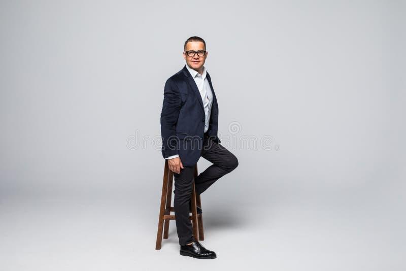 Hogere die Zakenmanzitting als voorzitter op witte achtergrond wordt geïsoleerd royalty-vrije stock afbeeldingen