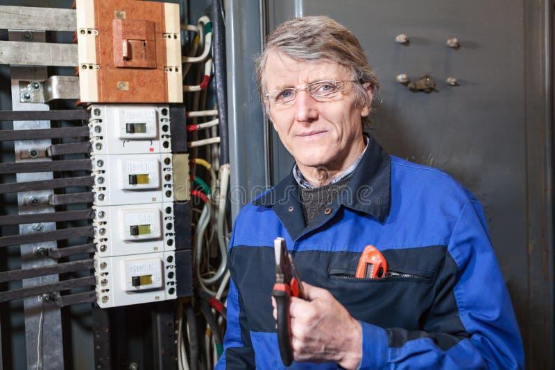 Hogere elektricien met buigtang in zijn handen die zich dichtbij hoogspanningspaneel bevinden stock afbeelding