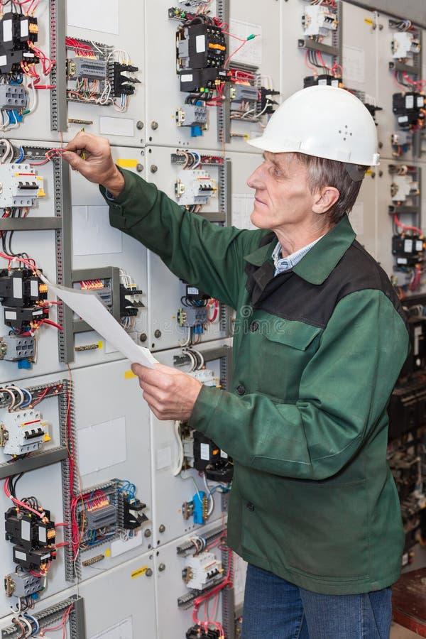 Hogere elektricien met een schroevedraaier en bedradingsdiagram in zijn hand die zich dichtbij een elektrisch schild bevinden royalty-vrije stock afbeeldingen