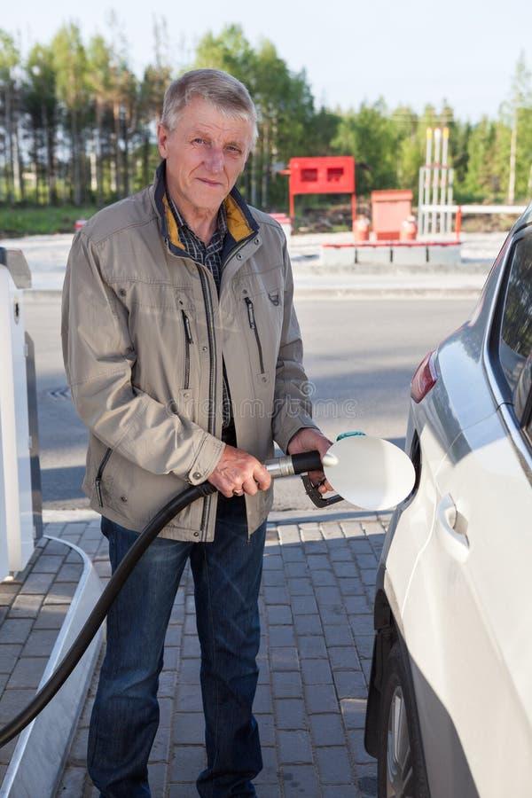 Hogere Europese mens die eigen auto vullen met benzine in benzinestations royalty-vrije stock fotografie
