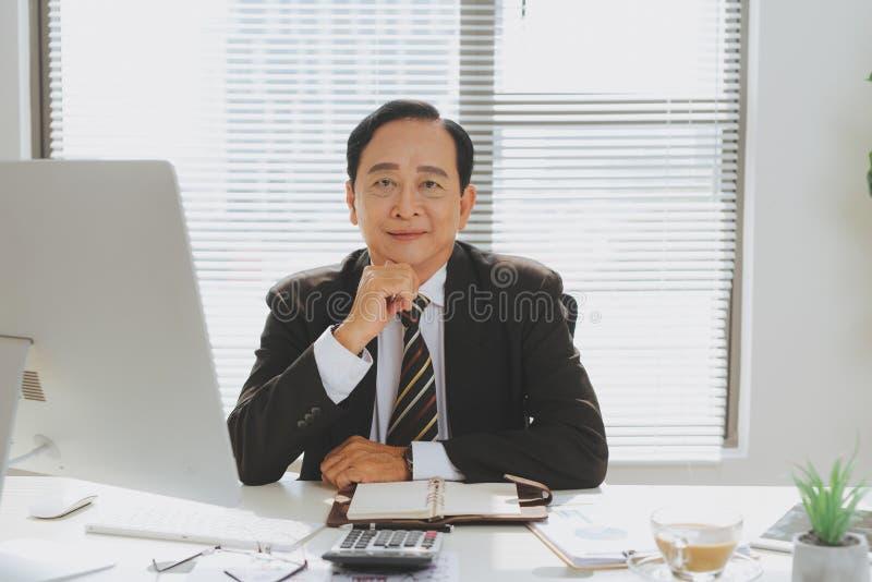 Hogere financiële Aziatische zakenmanzitting bij zijn werkstation binnen stock foto's
