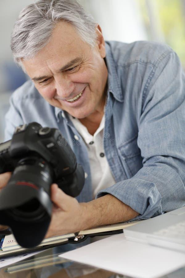 Hogere fotograaf die reflexcamera met behulp van royalty-vrije stock afbeelding