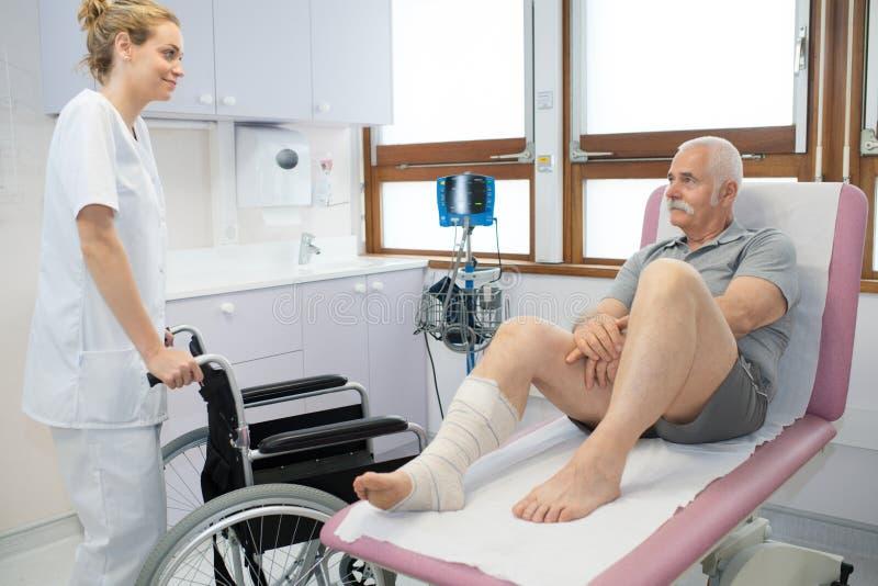 Hogere geduldige zitting die in het ziekenhuis op verpleegster met rolstoel wachten stock foto