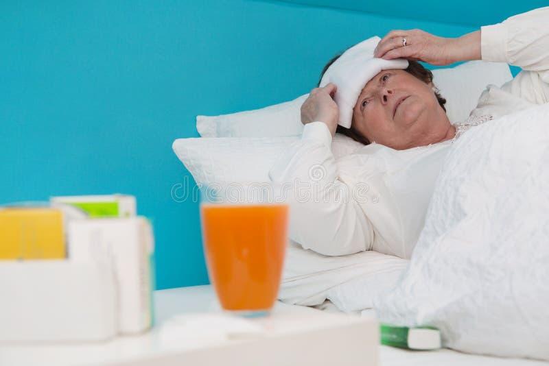 Hogere gelegd vrouw ziek in het bed met geneesmiddel en hoofdkussens, royalty-vrije stock afbeeldingen