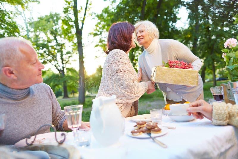 Hogere gelukwensende vrouw met gift bij verjaardag royalty-vrije stock afbeeldingen