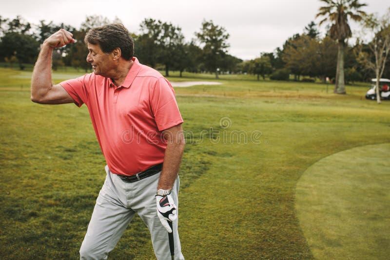 Hogere golfspeler die een gat op groen vieren stock foto
