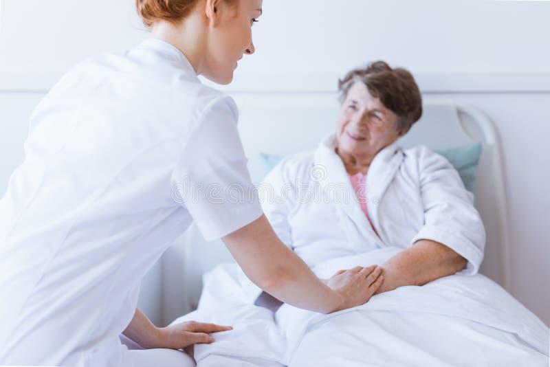 Hogere grijze vrouw die in wit het ziekenhuisbed liggen met jonge nuttige verpleegster die haar hand houden royalty-vrije stock fotografie