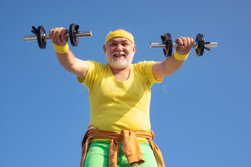 Hogere het Opheffen van de Mens Gewichten Hogere mens die in gymnastiek met gewichten uitwerken Gelukkige hogere mens die met dom royalty-vrije stock foto