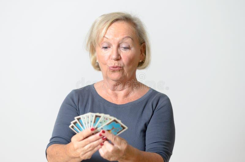 Hogere het Tarotkaarten van de Vrouwenholding tegen Gray Wall royalty-vrije stock afbeelding