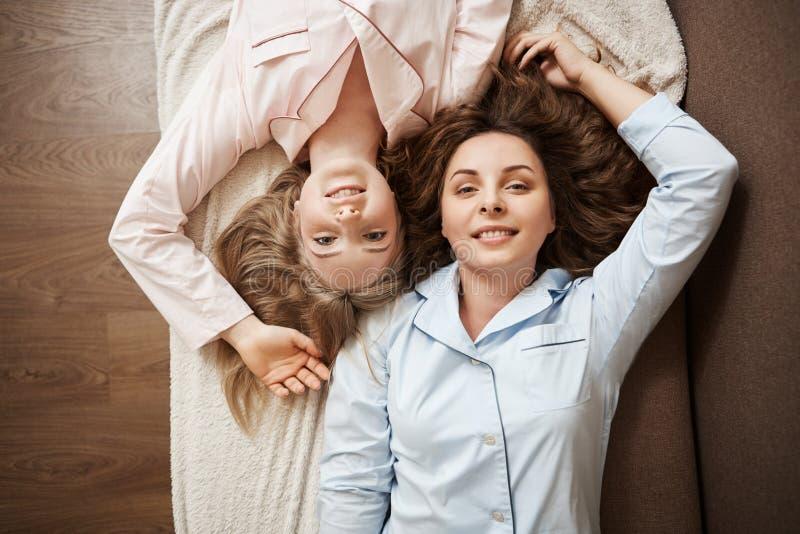 Hogere hoekfoto van twee aantrekkelijke Kaukasische vrouwelijke modellen die op bank in comfortabele pyjama, wat betreft hoofden  stock fotografie