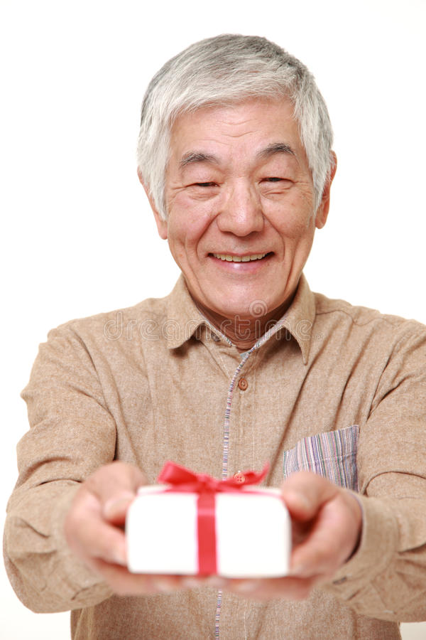 Hogere Japanse mens die een gift aanbieden stock afbeelding