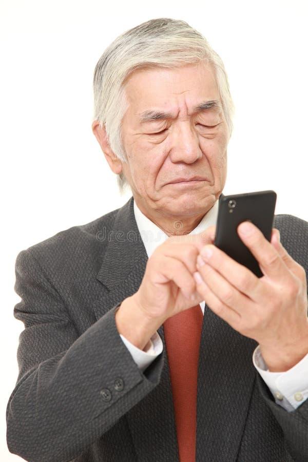 Hogere Japanse zakenman die slimme telefoon met behulp van die verward kijken stock foto