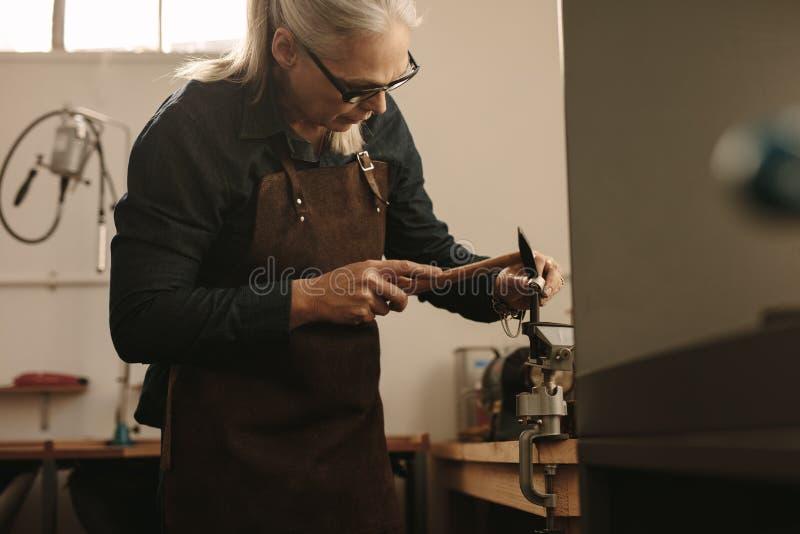 Hogere juwelier die en een zilveren ring gestalte geven ontwerpen stock afbeeldingen