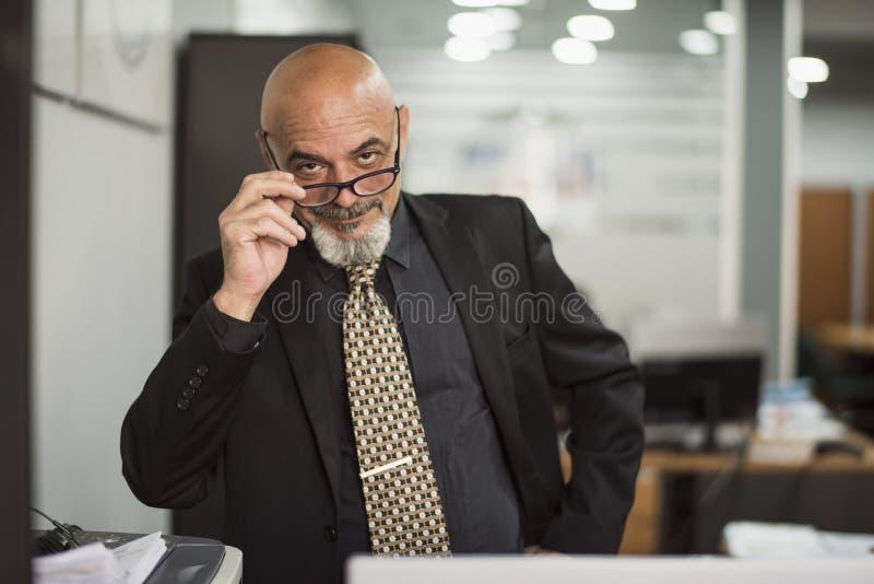 Hogere kale mens die in bureau met zwart kostuum werken stock foto