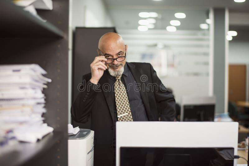 Hogere kale mens die in bureau met zwart kostuum werken royalty-vrije stock afbeelding