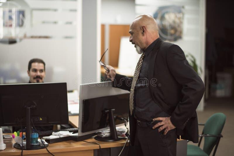 Hogere kale mens die in bureau met zwart kostuum werken stock fotografie