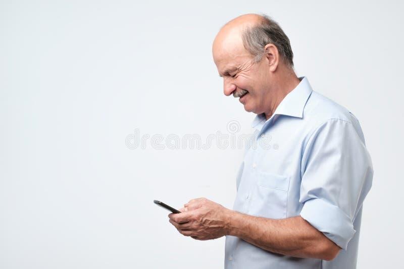 Hogere kale mens die mobiele telefoon bekijken royalty-vrije stock foto