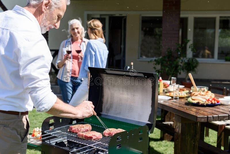 Hogere man die barbecue maken bij openluchtgrill terwijl vrouwen die wijn erachter drinken stock fotografie