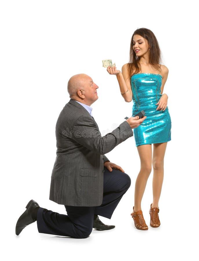 Hogere man die met geld aan jonge vrouw op witte achtergrond voorstellen Huwelijk van gemak stock foto's