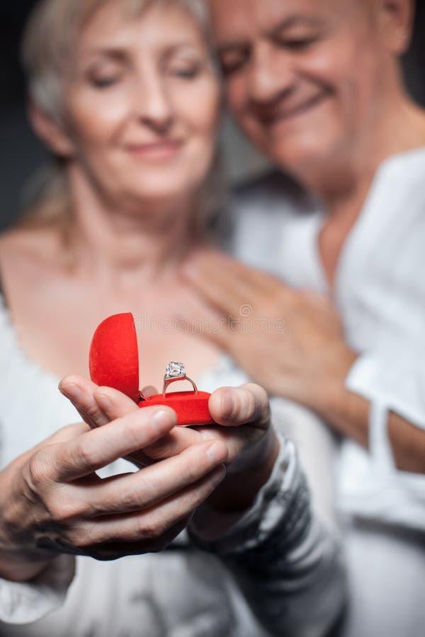 Hogere man die voorstel doen aan oudere vrouw; stock foto