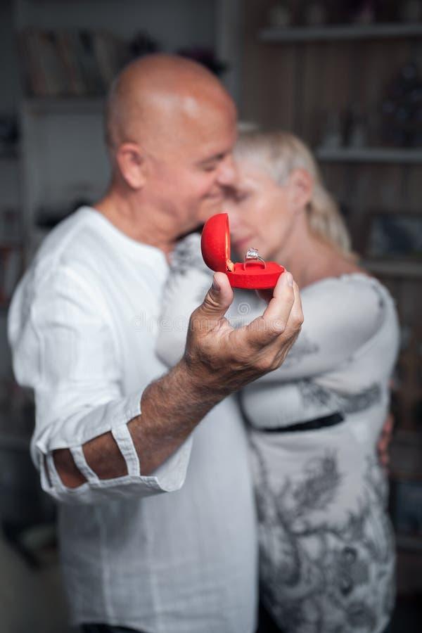 Hogere man die voorstel doen aan oudere vrouw; stock fotografie