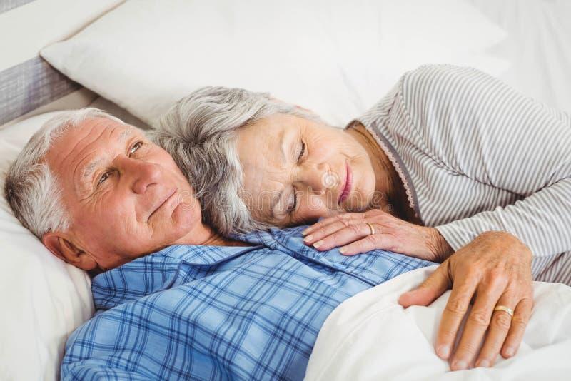 Hogere man die wakker naast in slaap hogere vrouw liggen stock afbeelding