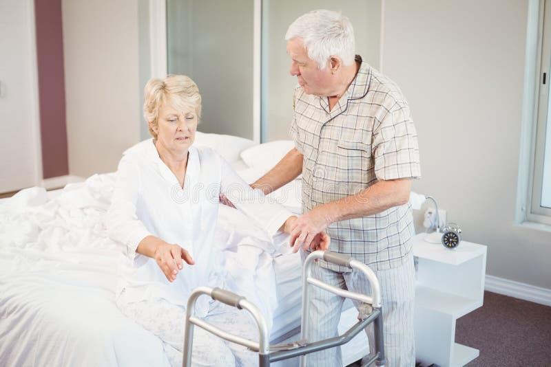 Hogere man die zieke vrouw helpen bij het opstaan van bed royalty-vrije stock afbeeldingen