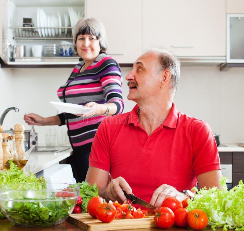 Hogere man en rijpe vrouw in keuken stock afbeeldingen