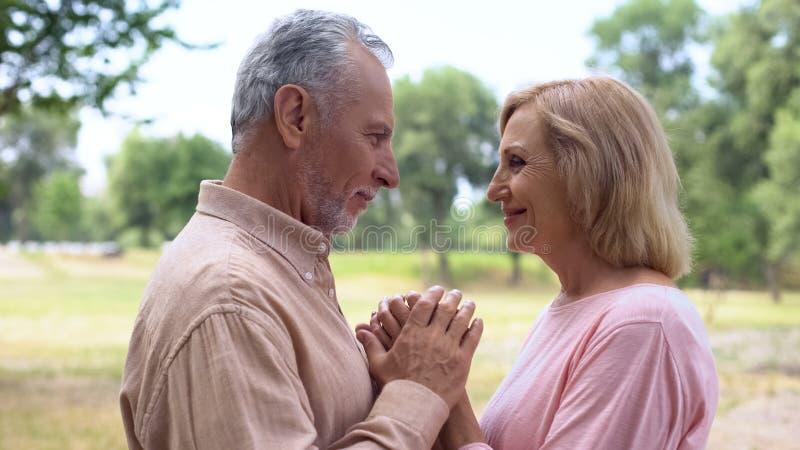 Hogere man en vrouwenholdingshanden, die elkaar met liefde, gelukkig paar kijken royalty-vrije stock foto's