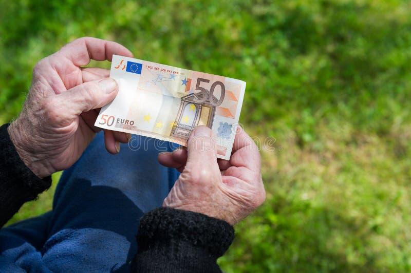 Hogere man handen die Euro bankbiljet houden Worstelend gepensioneerdenconcept stock fotografie