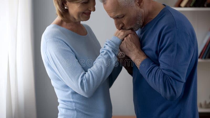 Hogere man holding en het kussen van de vrouw handen, dame die op datum, aantrekkelijkheid flirten stock afbeeldingen