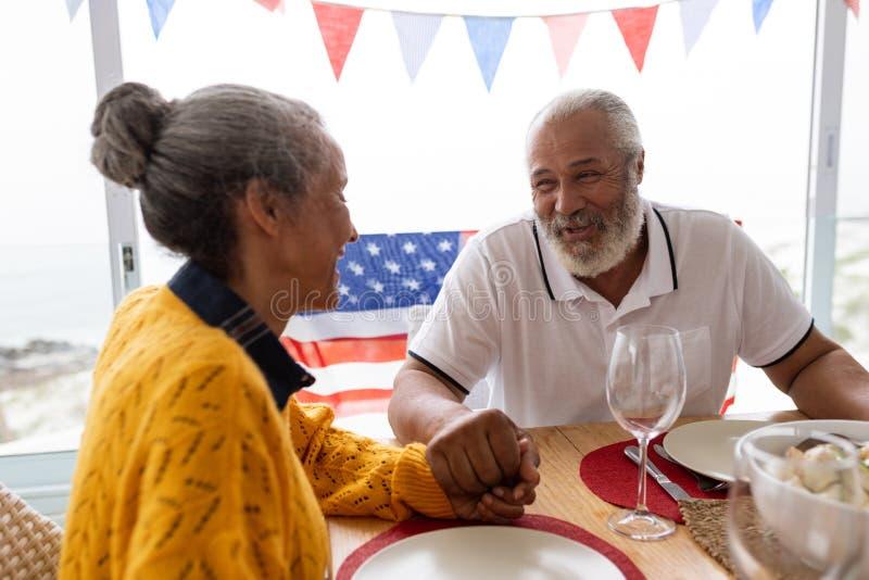 Hogere man holdingshanden van hogere vrouw terwijl het hebben van maaltijd op een eettafel stock foto