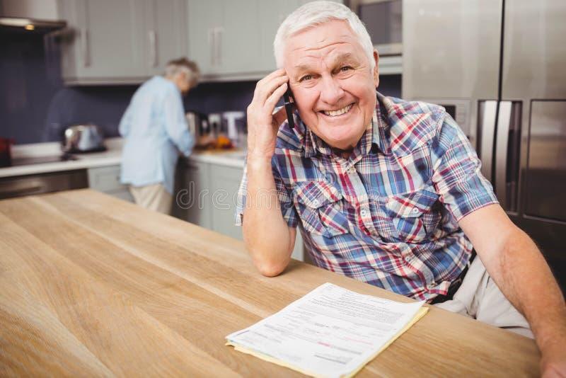 Hogere man op telefoon spreken en vrouw die in keuken werken stock foto's