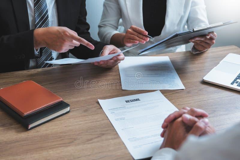 Hogere manager u die een samenvatting lezen tijdens een van de de werknemers jonge mens van het baangesprek een de vergaderingska royalty-vrije stock afbeeldingen
