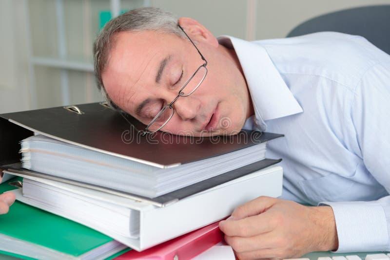 Hogere mannelijke accountantsslaap op lijst stock foto's