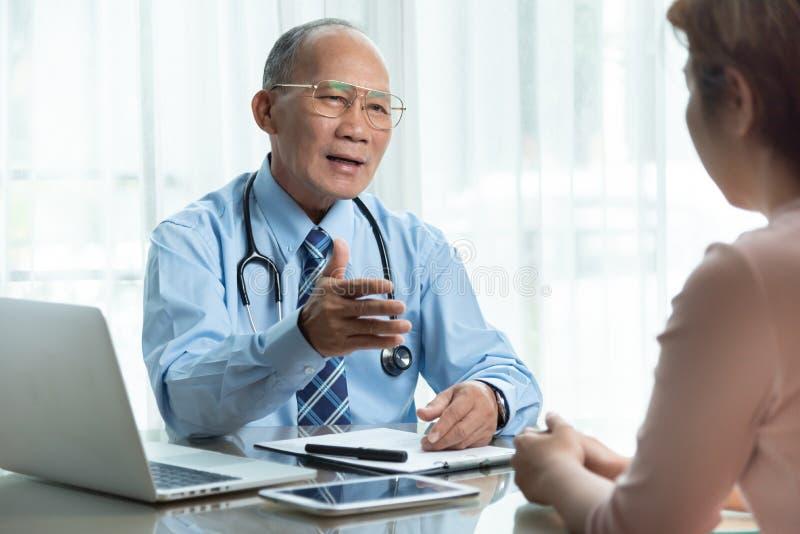 Hogere Mannelijke arts in blauw overhemd die met vrouwelijke patiënt spreken royalty-vrije stock afbeeldingen