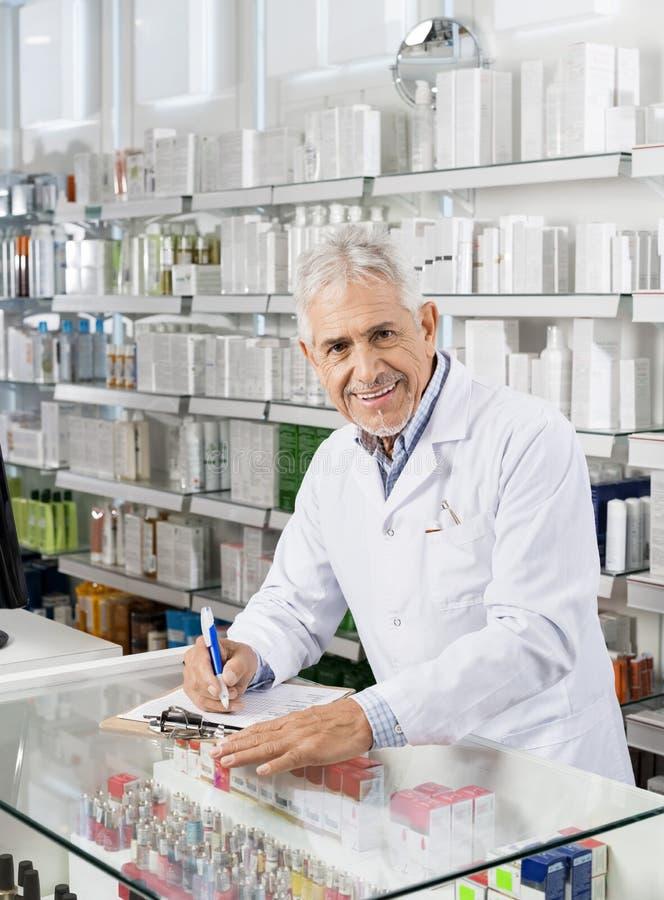 Hogere Mannelijke Chemicus Writing On Clipboard in Apotheek stock foto's