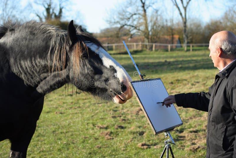 Hogere mannelijke kunstenaar die een paard schetst. stock afbeelding