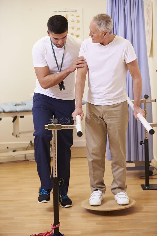 Hogere Mannelijke Patiënt die Fysiotherapie in het Ziekenhuis hebben stock afbeeldingen