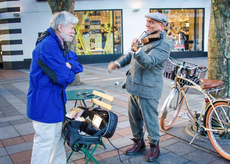 Hogere mannelijke praatjes met straatmusicus stock fotografie