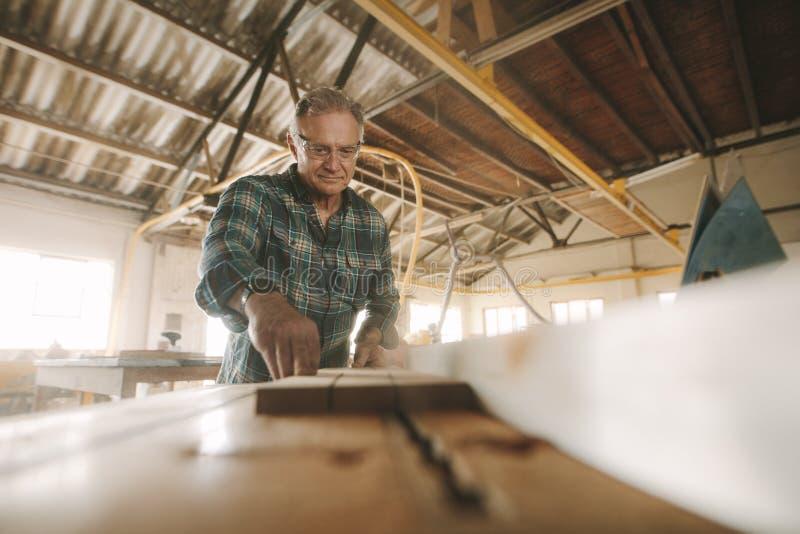 Hogere mannelijke timmerman die in timmerwerkworkshop werken stock foto's