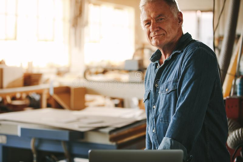 Hogere mannelijke timmerman die zich in zijn workshop bevinden royalty-vrije stock foto