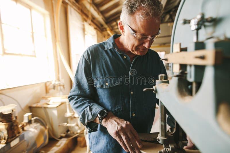 Hogere mannelijke timmerman die in zijn workshop werken stock foto's