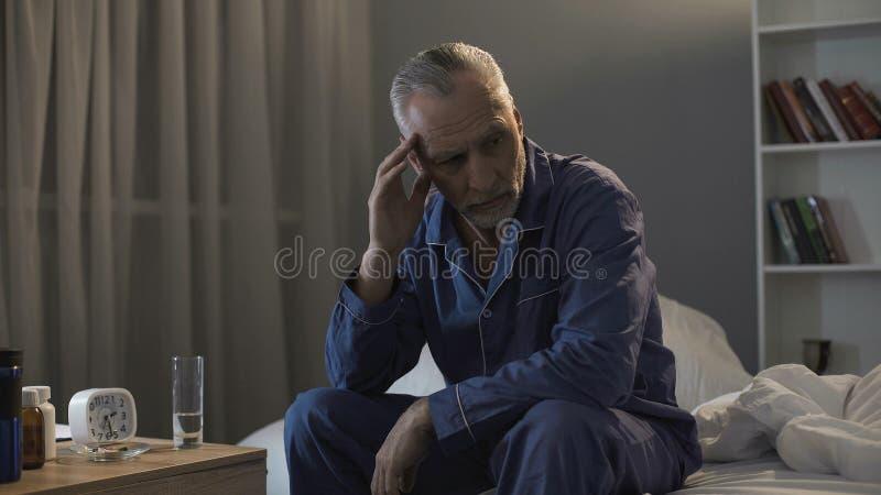 Hogere mannelijke zitting in bed en het lijden aan vreselijke hoofdpijn bij nacht stock fotografie