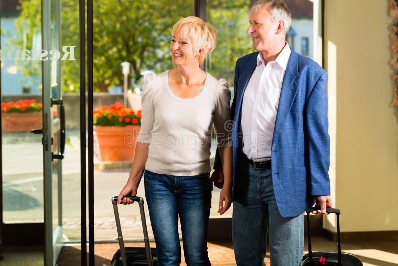 Hoger echtpaar die bij Hotel aankomen stock afbeeldingen