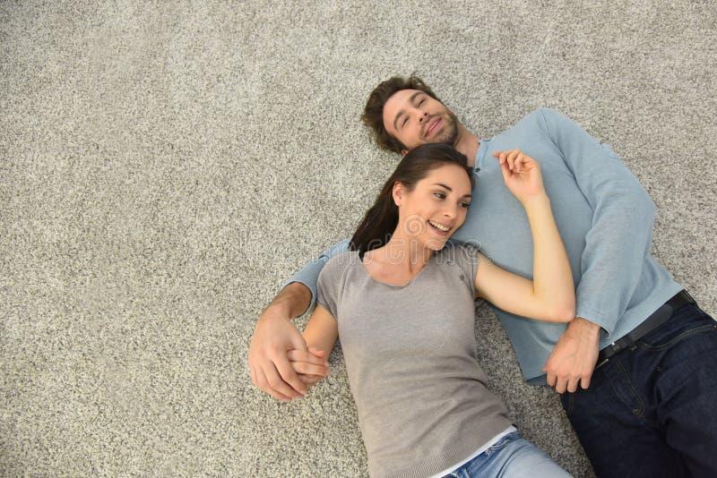 Hogere mening die van paar op tapijtvloer liggen stock foto's