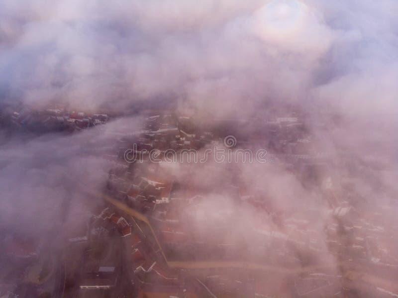Hogere mening van rode daken van kleine stad dichtbij rivier onder heuvels tegen blauwe hemel en witte wolken stock fotografie
