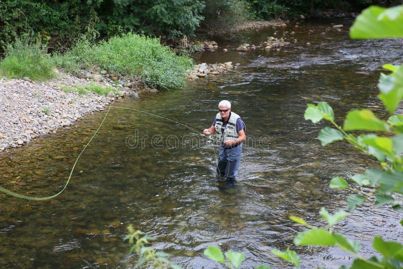 Hogere mening van visser die goede tijd visserij besteden stock afbeelding