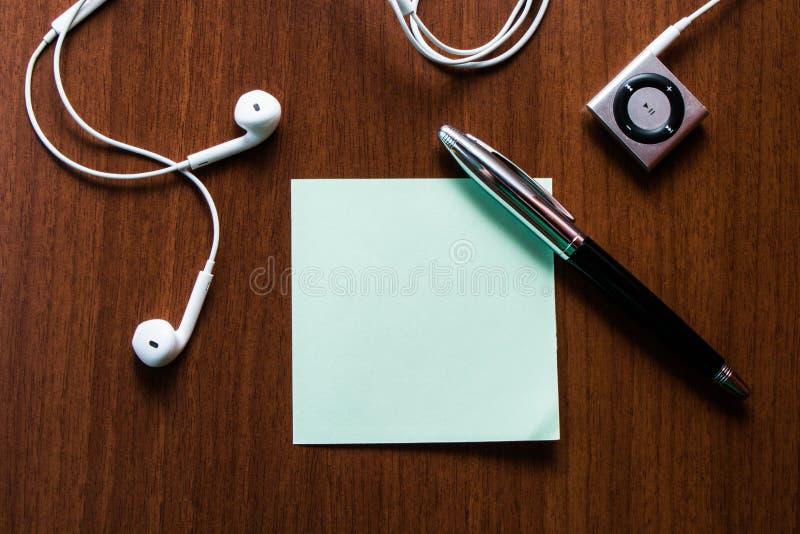 Hogere menings vastgestelde oortelefoons die de nota van het de stokstootkussen van het muziekapparaat liggend horen op houten li royalty-vrije stock foto