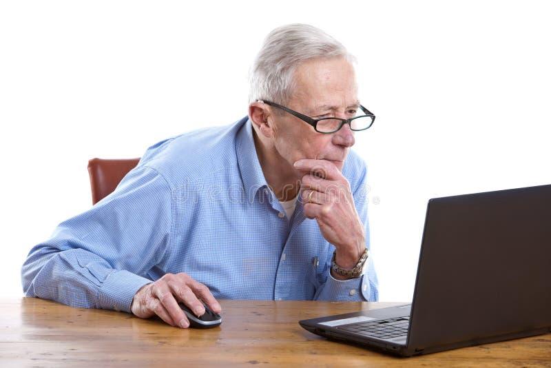 Hogere mens achter de computer stock foto's